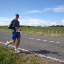 Gerry with the typical rolling green Kiwi hills dotted with cows or sheep.