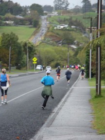 Runners in the distance making their way up a hill.