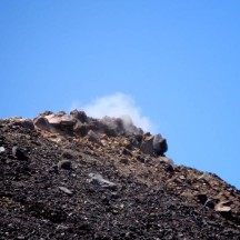 Whiffs of smoke rising from the crater rim.