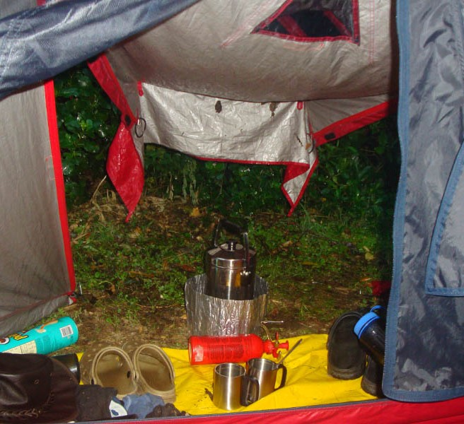 A pot of morning coffee, with the tent flap providing some shelter from the rain.