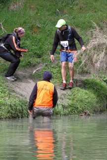 Wouna negotiating the best way down the riverbank. I cannot imagine how cold this marshall must have been, after standing in the river for who knows how long to help us poor runners across the water obstacle. (Photo: Supersport Images)