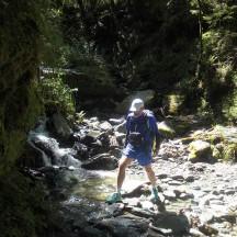 Boulder hopping across a little stream.