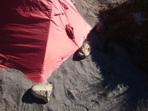Stacking sand over the sides of the flysheet to avoid the wind turning the tent into a giant red kite.
