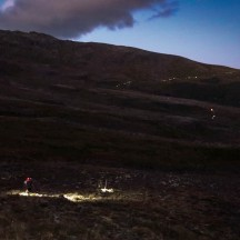 Hundreds of headlamps snaking up the mountainside.